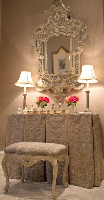Elegant draped dressing table and ornate Venetian mirror.
