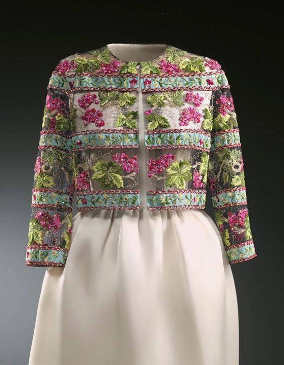 This evening dress was designed by Balenciaga in Paris for the 1959 winter collection and worn by Mona Bismarck. The other example on this page was worn by Princess Grace of Monaco. The simple dress gives all the prominence to the minimalist-structured jacket, decorated with exquisite embroidery by François Lesage.   Cat. Mona Bismarck-Cristóbal Balenciaga March-May 2006, 82-83.   Cat. of the exhibition Les années Grace Kelly. Montecarlo, 2007.