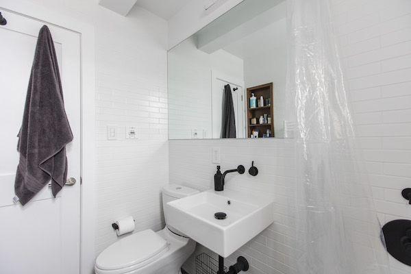 A wall-mounted WSBath sink has a slim footprint and helps make a small bathroom feel spacious.