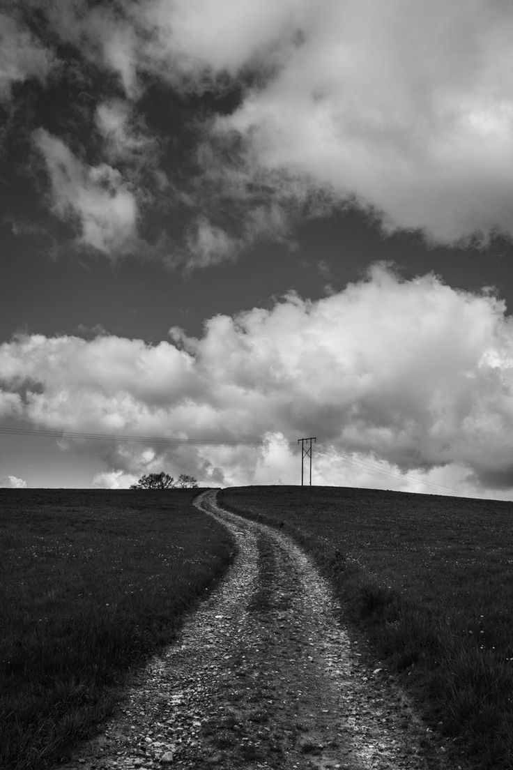 Free download of this photo: https://www.pexels.com/photo/gray-scale-photography-of-grass-field-under-cloudy-sky-196226/ #black-and-white #road #landscape