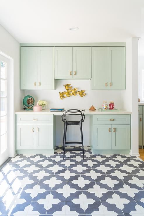 Mint green kitchen features a built in island height desk boasting mint green cabinets adorned with brass hardware paired with a sleek black stool, Kartell Masters Stool, alongside a white and blue Moroccan tile floor.