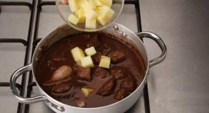 Tapa la olla y déjala silbar durante media hora. Aparta del fuego y deja que pierda presión de forma natural. Añade el chocolate rallado y remueve. Incorpora las patatas peladas y troceadas. Vuelve a cerrar la olla y deja silbar durante 8 minutos. Destapa la olla y sirve en cazuela de barro.