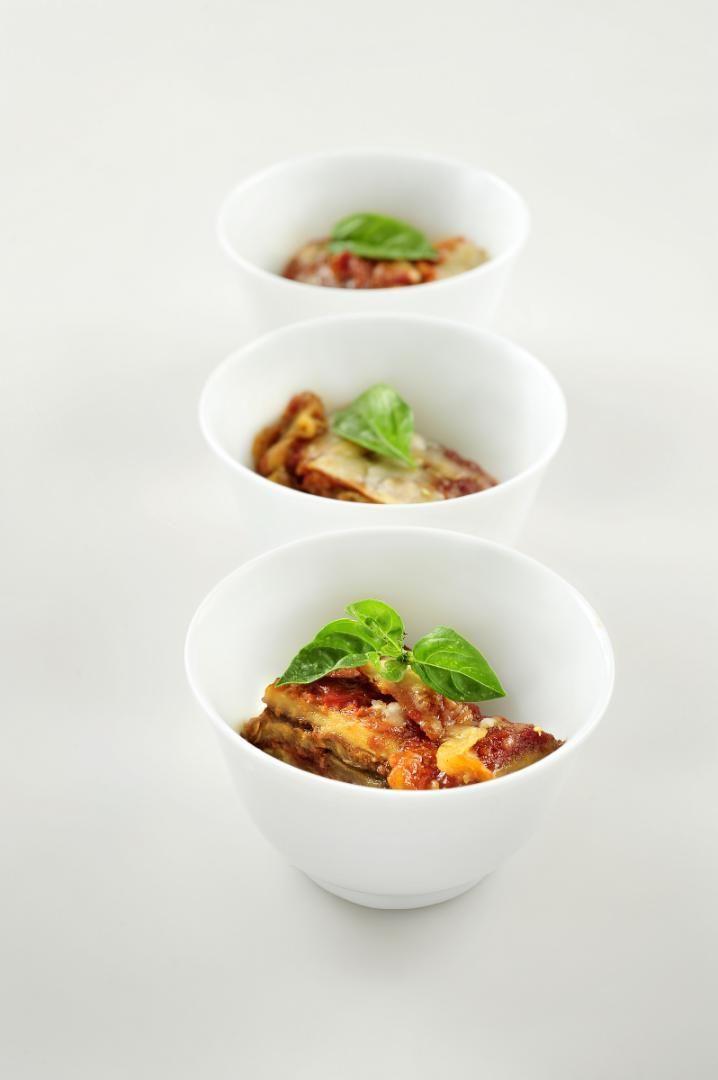 Bereiden:Snijd de aubergines in de lengte in plakken van ongeveer 2 cm dik. Kruid ze met peper en zout.Verhit een beetje olijfolie in een pan en bak de aubergineschijven aan beide kanten krokant. Doe dit in verschillende keren zodat ze naast elkaar in de pan kunnen liggen. Laat daarna uitlekken op keukenpapier.Ontvel de tomaten en snijd ze in stukjes. Stoof ze aan in een scheutje olijfolie en een fijn gesnipperd teentje knoflook. Kruid met peper en zout en laat sudderen tot een sm...