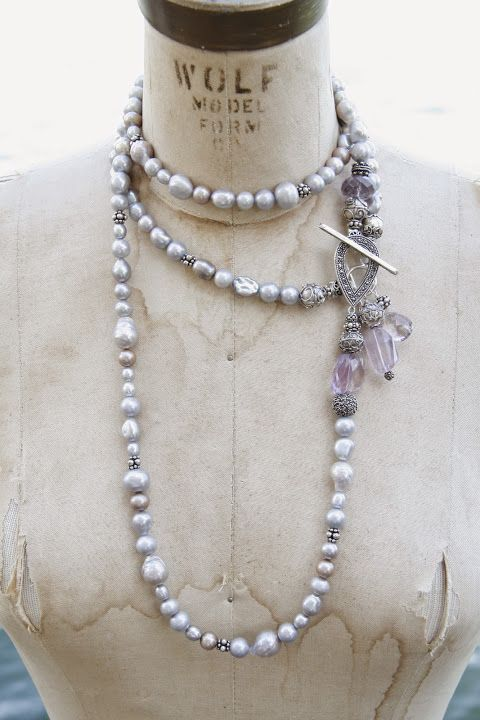 Two necklaces. A long rope of grey baroque pearls with sterling silver beads and a marcasite toggle. And a short grey pearl necklaces with lilac amethyst fobs.