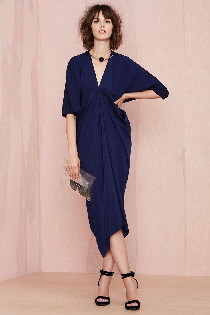 This kimono-inspired navy dress features a V neckline, dolman sleeves, and a tapered fit. Unlined. Wear it with minimal heels and a bold lip color for that fancy event you're going to or rock it with slide sandals.
