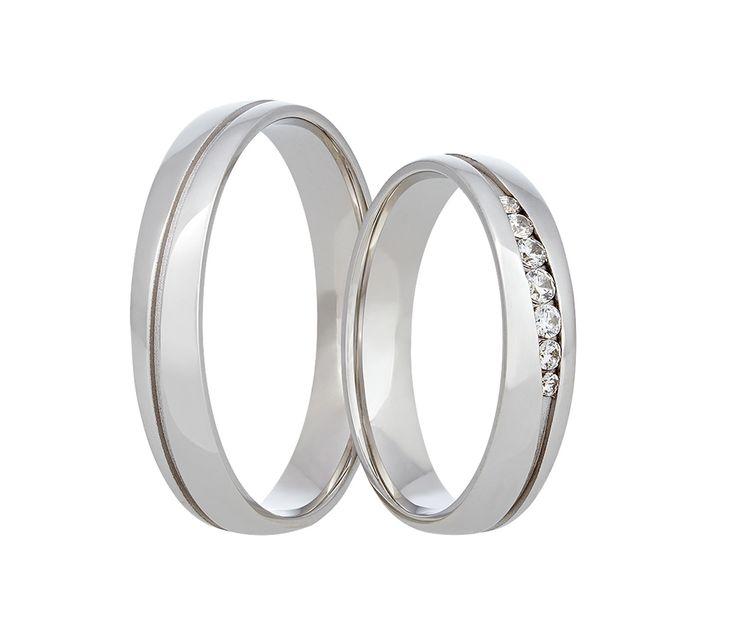 Jednoduché snubní prsteny vyvedené v bílém zlatě. Prostředkem obou kroužků se táhne jemná vlnovka, do které je u dámského prstýnku vsazeno sedm kamenů.
