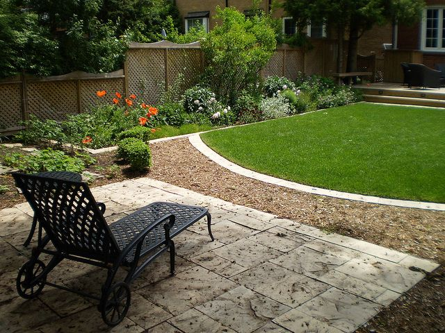A small backyard is transitioned to a lovely backyard retreat with flower beds, patio and even a place for the kids to play.