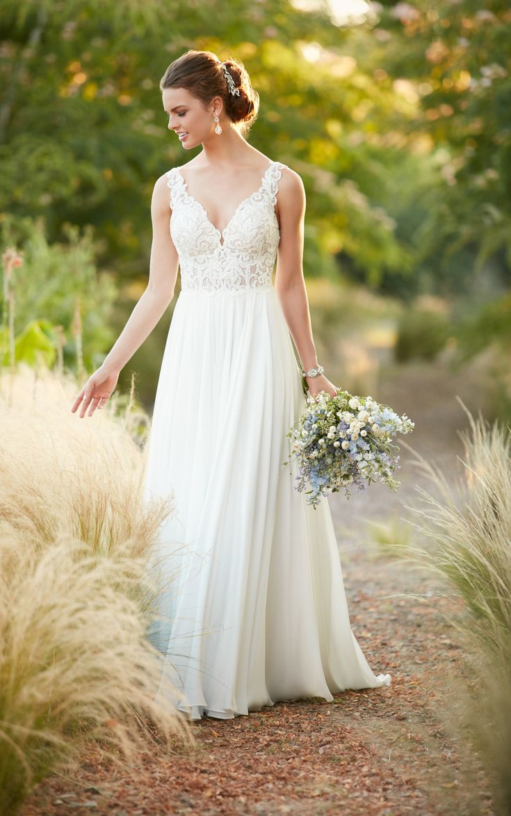 A modern update to the boho style, this chiffon wedding gown from Essense of Australia is perfect for a beach wedding! Soft, flowy, and light, this Lace and Crepe Chiffon sheath gown is both casual and elegant. Featuring a deep V-neckline, the French and cotton lace bodice and straps of this gown flow perfectly into a deep back, and feature architectural beading. The Crepe Chiffon skirt is lightweight and voluminous and flows elegant into the train. The back of this gown zips up beneath…