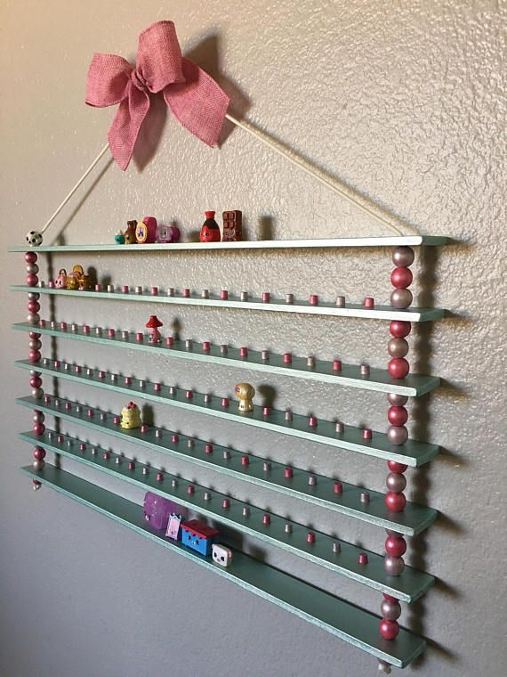 This Shopkins display shelf is perfect for storing some of your littlest toys! It has five shelves with 20 pegs on each to hold 100 Shopkins! The two additional shelves are greet for those without holes on the bottom, or for the extra Shopkins items. Keep you present boxes, gift bags, baskets, and more! These shelves are sturdy and stable thanks to the beads between each shelf. The cute bow at the top is great for hiding the nail or hook (not included) you decide to use to hang it from. Hang…