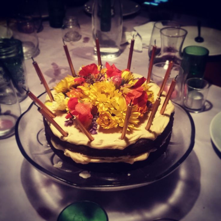 This cake! Where to begin.Two darkly moist layers of chocolate cake sandwiched together with salted caramel cream cheese icing and topped with a mountain of flowers. It's recently been made …