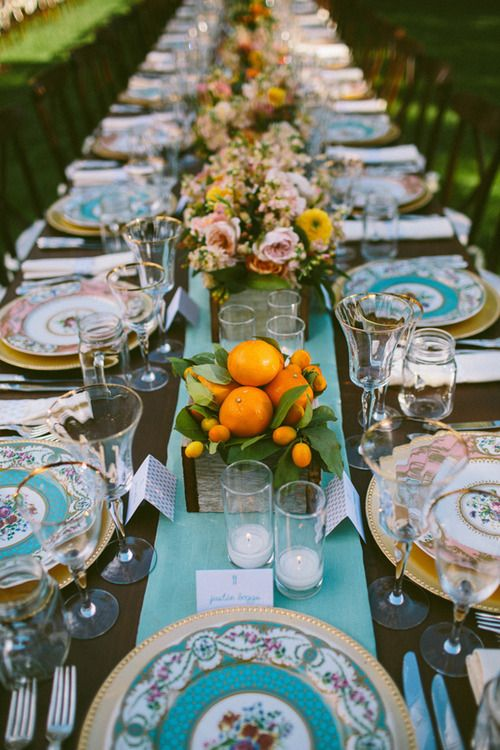 outdoor dining with fruit as centerpieces and a slim table runner in a bright color that matches the plates for a summer/spring outdoor meal