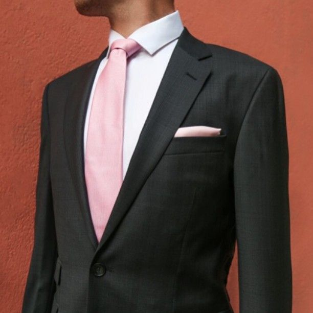 Look effortlessly stylish with a dark suit and matching pink accessories.