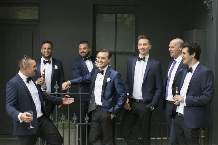 Groomsmen in their deep navy suits, Groom in a slightly glossier sheen of a suit