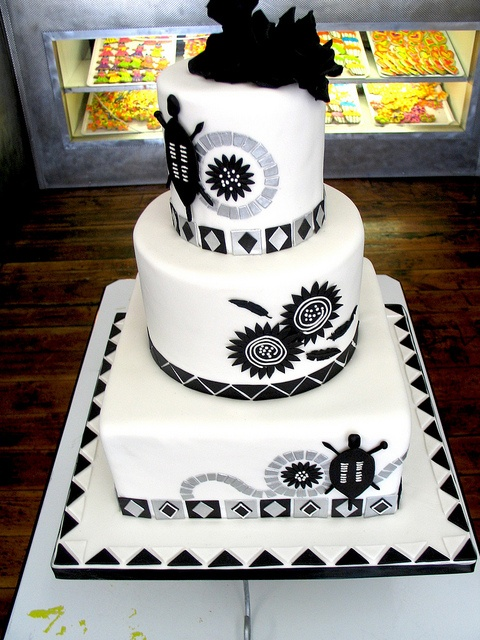 3-tier Wicked Chocolate wedding cake covered in white fondant decorated with black & silver traditional tribal designs & black fondant floppy roses by Charly's Bakery, via Flickr