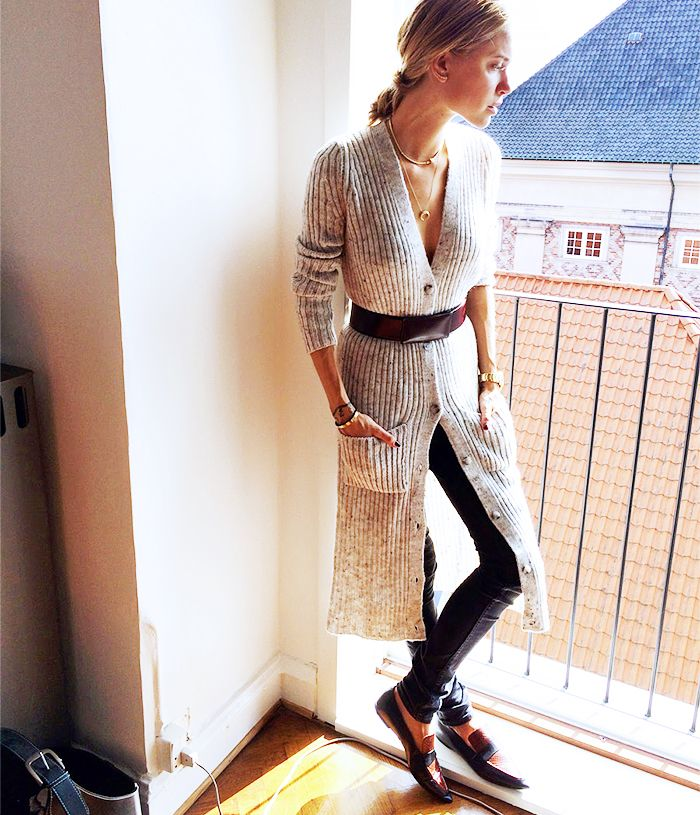Pernille Teisbaek wearing a long cardigan, belted at waist, black skinny jeans, and loafers