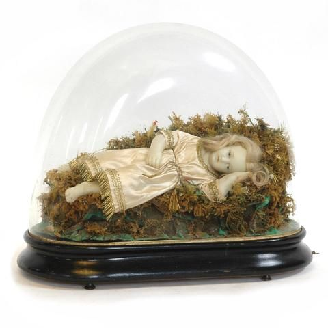 Enfant Jésus en cire sous globe socle musical à deux airs en bois noir, remontage par tirage. Bon état général. Epoque Napoléon III. 60X29 cm - H. 53 cm.