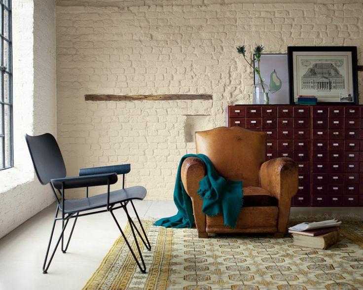 Pour une ambiance rustique, pensez aux teintes naturelles. La brique apparente d'un ton crème chaud de ce salon se marie harmonieusement avec les meubles en bois et cuir, pour un look bohême et industriel.