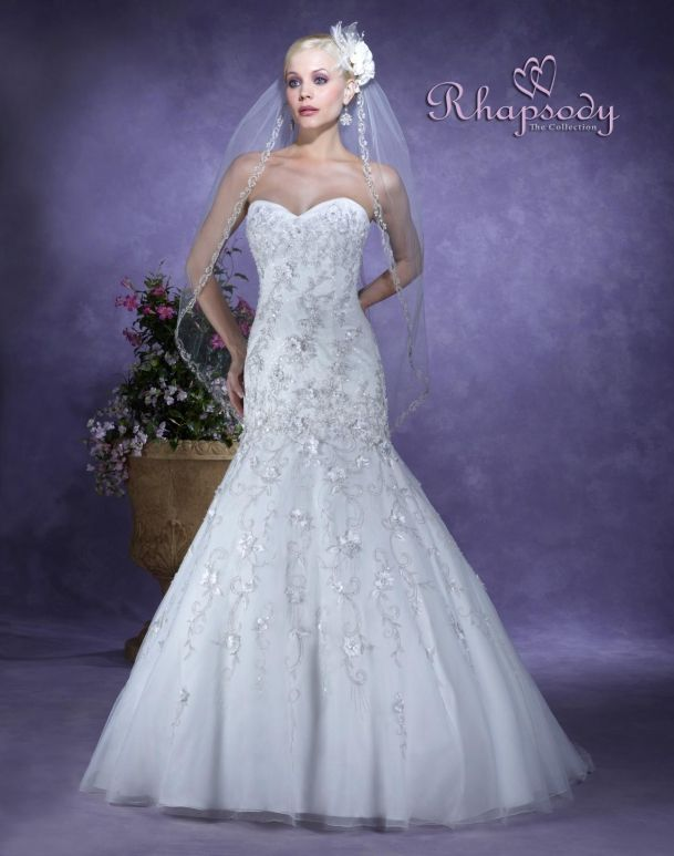 Rhapsody  Style #R7101  Elegant wedding gown has dropped waist, satin torso and fine English netting over organza. The skirt is articulated with lovely embroidery and floral lace appliqués! There is sweetheart neckline, a lace up back and chapel train.