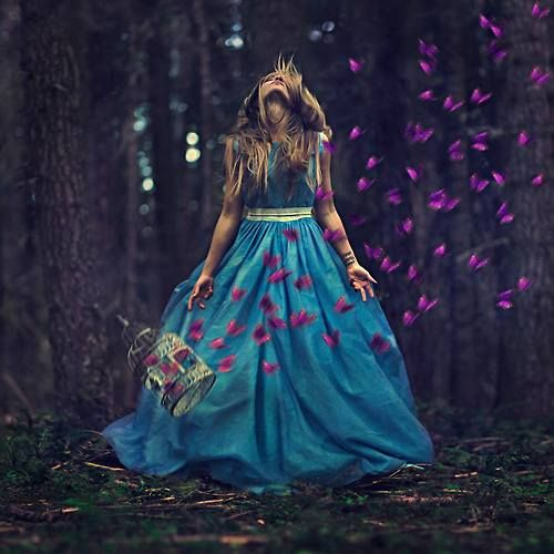 The forest maiden in the blue dress, with an open cage full of butterflies | pink and turquoise | magic fantasy photo