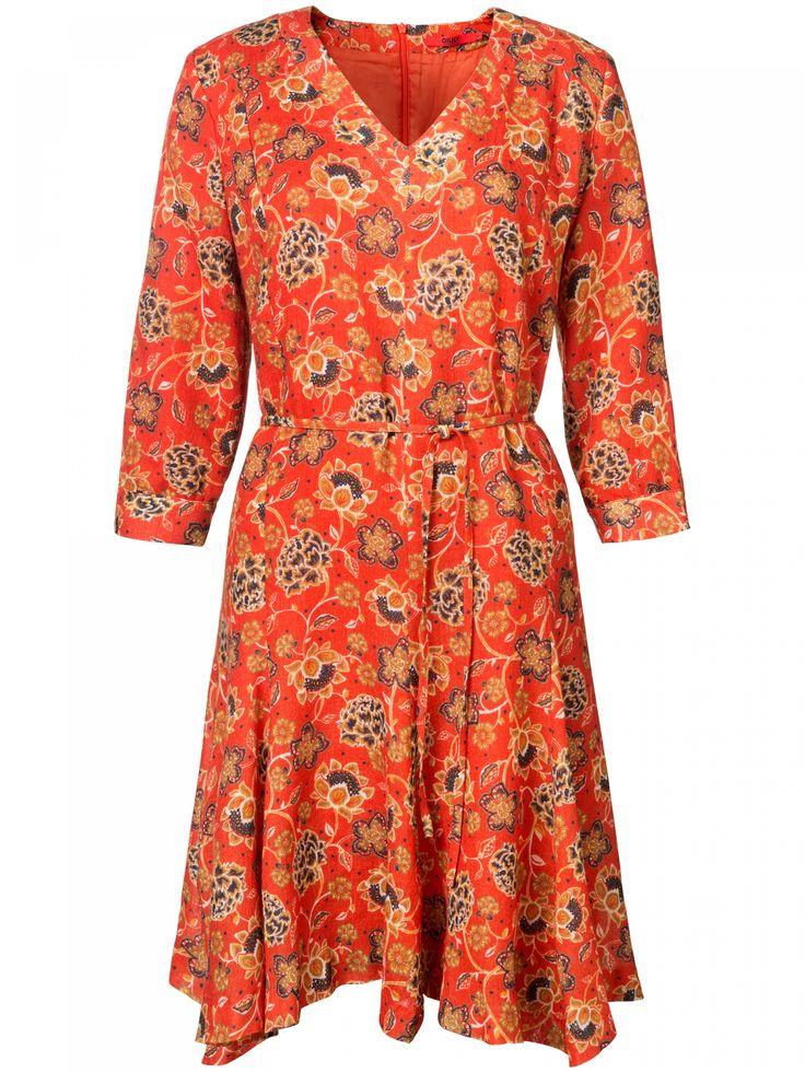 Soepele wollen jurk met kleurrijke Oilily-print in warmoranje. De wijde rok, licht wijde mouwen en het ceintuurtje geven de jurk haar vrouwelijke pasvorm.