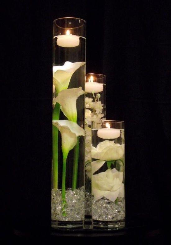 19. Centros de mesa en base de vidrio con alcatraz, velas y flores