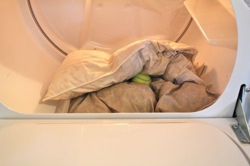 """place pillows in the dryer with a couple of tennis balls to help get them back to their """"fluff stage"""" and kill germs with the high heat."""