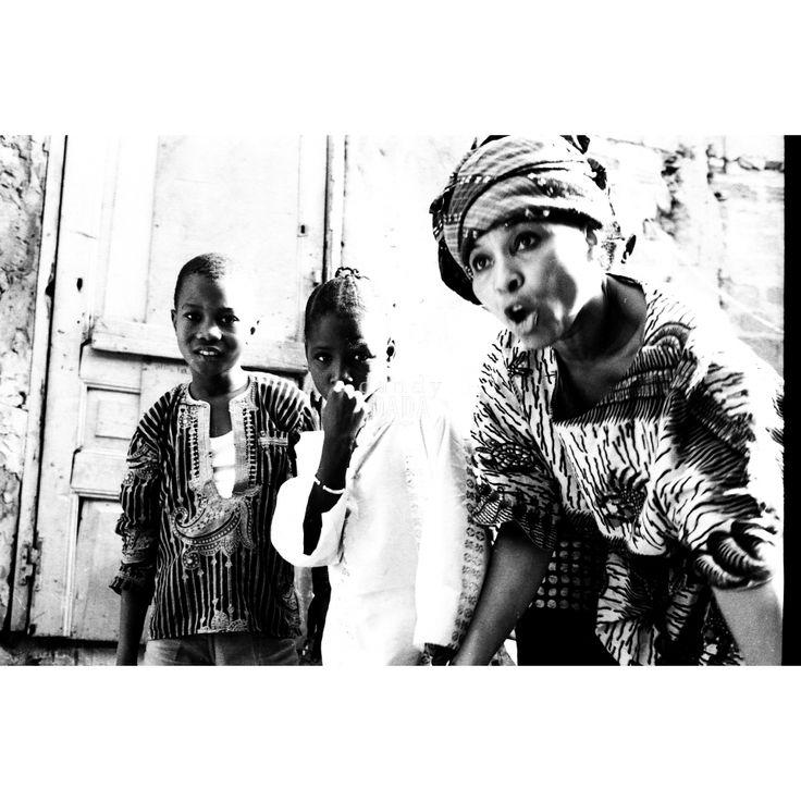 """The voice of Nigeria Opera scattata in una strada di un villaggio nigeriano. L'attenzione è catalizzata sugli """"anonimi"""", considerati più interessanti, più """"degni di essere fotografati"""". Il reportage, dell'agenzia """"D.F.P."""" di Dani Maria Turriccia, si distingue per il suo forte contrasto chiaroscurale, che accresce l'impatto emotivo. Africa, Nigeria 1975."""