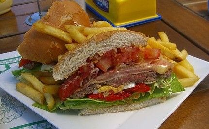 """The chivito, the national sandwich of Uruguay. """"Your typical chivito is jammed with thin slices of beef, crispy bacon, mozzarella, lettuce, tomato and fried eggs, with perhaps a slathering of mayo.""""  Good grief.  I wish that I had one right now!"""