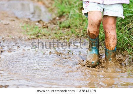 Child's feet stomping in a mud puddle. - stock photo