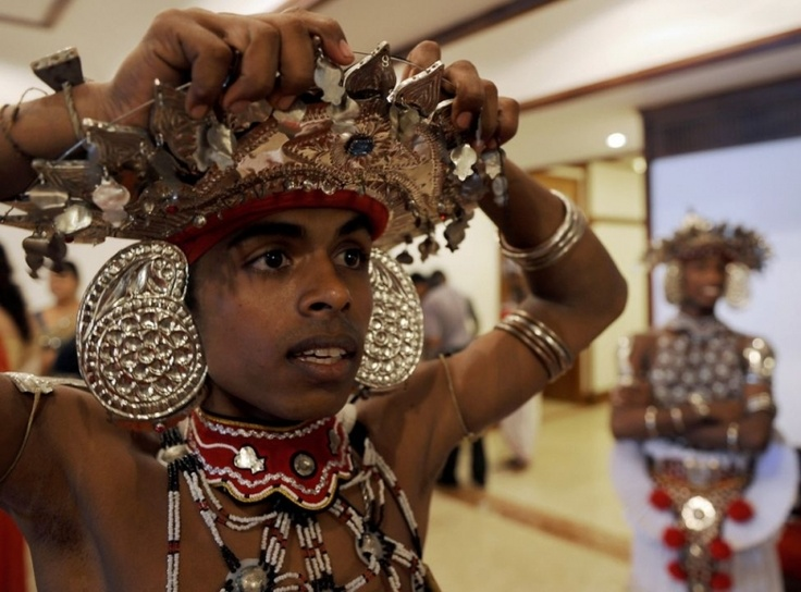 Танцор со Шри-Ланки поправляет украшения на своем головном уборе в преддверии богатой свадебной церемонии в Коломбо. Свадьбы в этой стране с 20-миллионным населением – событие особое, и родители начинают собирать на нее деньги сразу после рождения ребенка. (Ishara S. Kodikara - AFP/Getty Images)