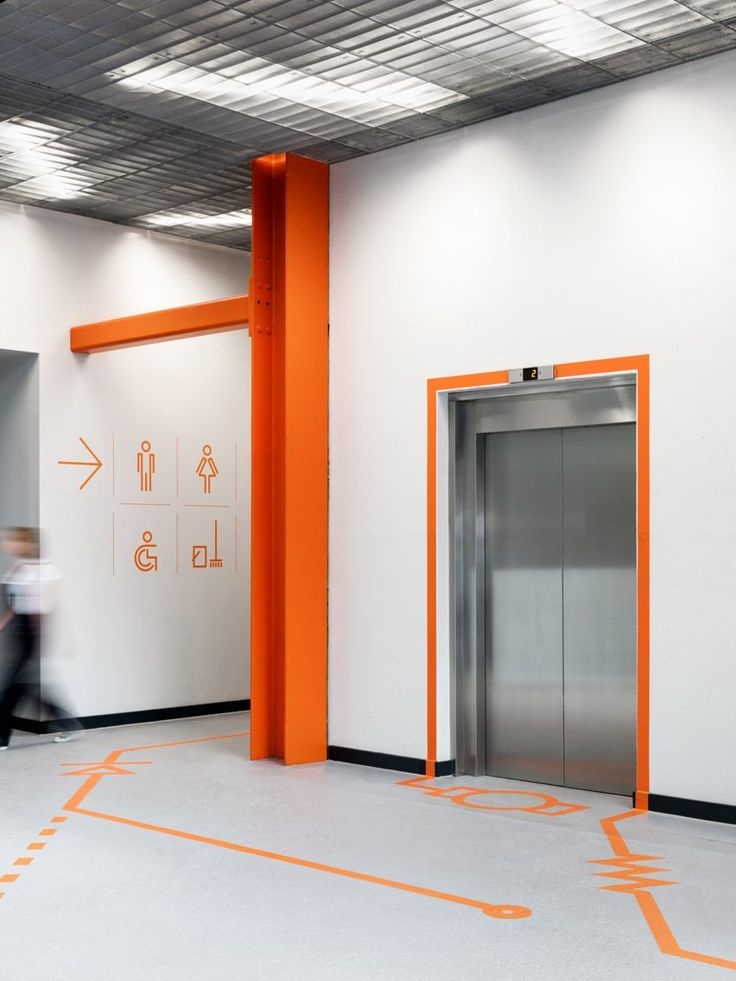 Inside this building, large bright orange graphics placed on the walls and floors guide visitors to different areas. The signage uses lines and symbols based on those found in electronic diagrams.