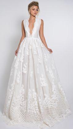 Vestido de noiva longo com decote profundo, sem mangas e cheio de aplicações em renda. Romântico!
