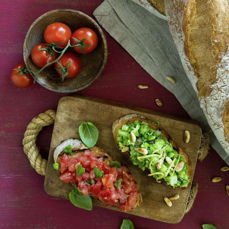 Broccoli- und Tomaten-Crostini. Geröstetes Baguette, einmal belegt mit Broccoli, Pinienkernen, Sardellenfilets und Kapern, einmal mit Tomaten, Basilikum, Knoblauch und Gewürznelken.