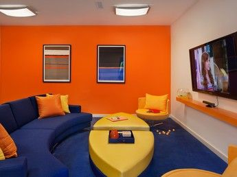 Awesome gaming room!  Bright orange wall with yellow and blue furniture.  Screams MAN CAVE!  Could use more exciting light fixtures.