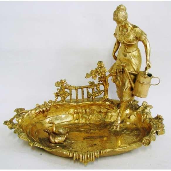 Belo centro de mesa em metal banhado de dourado, com influência Art-Noveau, na forma de lago com patinhos, e adornado com figura de camponesa com balde. (dourado com estofados devido ao desgaste do tempo). Med. 31x387x25cm.