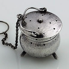 """Fradley Hammered Sterling Silver Tea Ball A Fradley sterling silver tea ball with a hammered finish and three supporting legs. The lid hinges back to open. Height: 1 1/4"""". marked on the inside lip"""