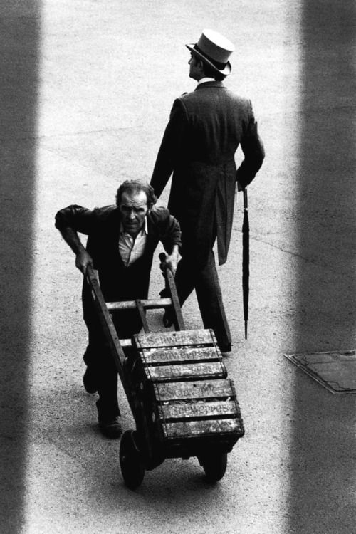 A top-hatted man passes a workman pushing a crate of beer, highlighting…