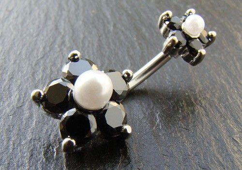Piercing nombril double charmes : http://www.aiapiercing.com/piercing-nombril-double-fleur-cristaux-noirs-et-perles-nacrees Ce piercing non pendant est composé d'une double fleur ornée d'une perle nacrée en son centre, entourée de 5 pétales de pierre de zircon noire. Le matériau utilisé pour ce piercing est de l'acier chirurgical 316L, la tige est de diamètre 1,6mm et sa longueur est 10mm. La fleur du bas est fixe et mesure 12mm. La circonférence de la fleur du haut est de 8mm.