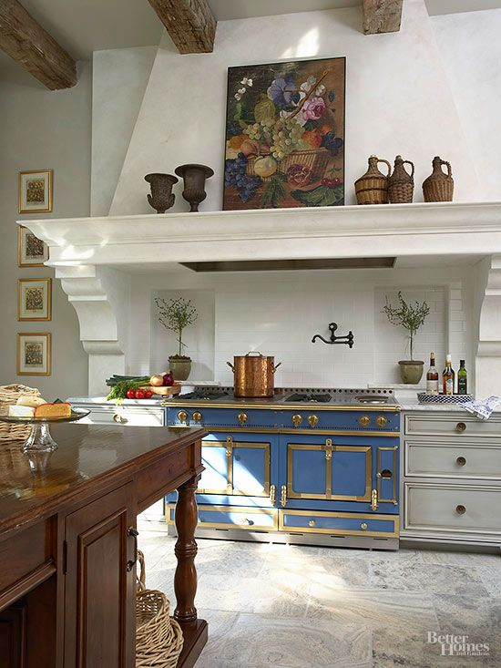 Captivating details draw eyes toward the range wall. A stone mantel spans the stove and adjacent base cabinets, unifying the area. Vintage artwork and sculptures align on the mantel to break up the expansive chimney's flat plane. A blue range with brass details demands attention.