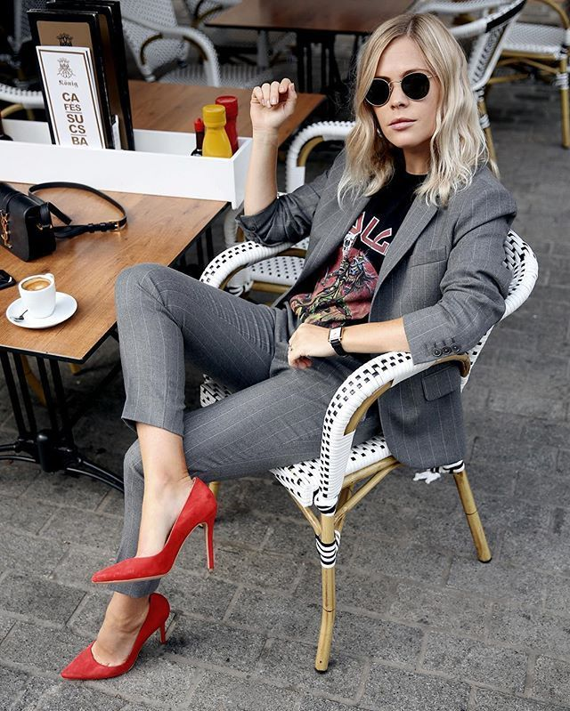 Give a classic pantsuit some edge by pairing it with a band tee and red pumps. Jesse Bush