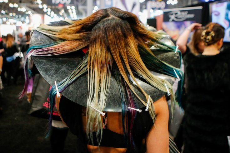 A woman has her hair done as people visit the International Beauty Show New York at Javits Center in New York