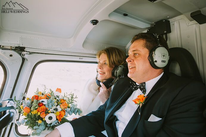 bride and groom in helicopter flying to the snow on Cecil Peak