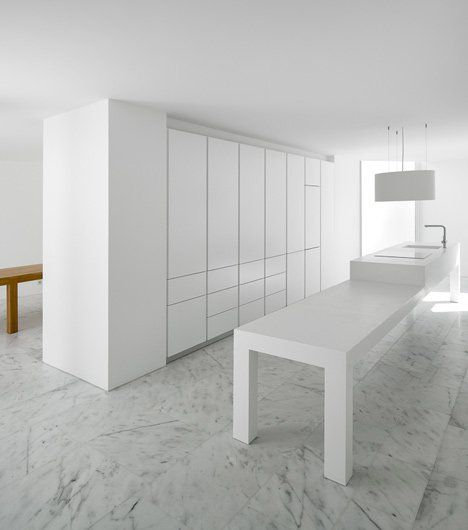 Storage cupboards blend into a thick partitioning wall that separates the kitchen from the rest of this three-storey house in Alcobaça, designed by Portuguese studio Aires Mateus.