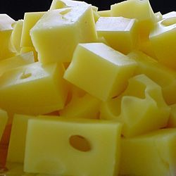 """Swiss cheese is a generic name for several related varieties of cheese which resemble the Swiss Emmental. Some types of Swiss cheese have a distinctive appearance, as the blocks of the cheese are riddled with holes known as """"eyes"""". Swiss cheese has a savory, but not very sharp, taste"""