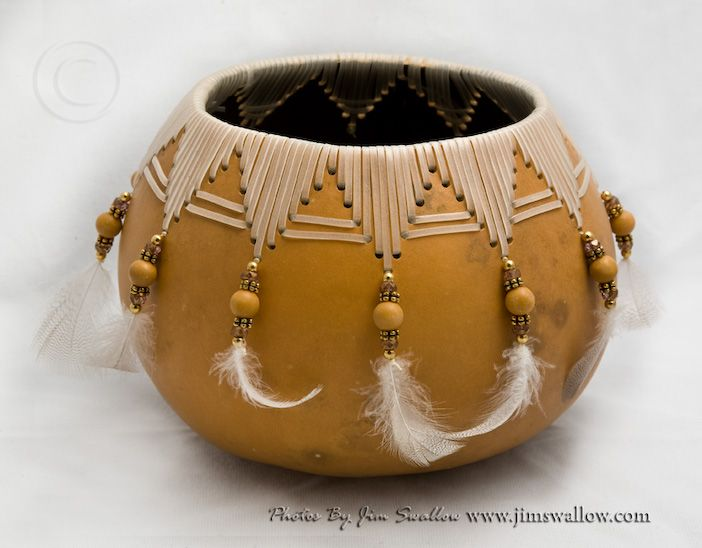 By Jim Swallow. Tan finished,natural gourd with weaving, beads and feathers. 5.5 inches high and 7 inches wide