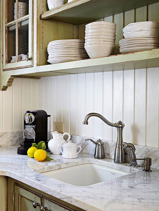 Classic materials, aged finishes, and casual luxury make for an inviting place to cook and gather. Combining the elegance of Carrara marble countertops with a charming tongue-and-groove board kitchen backsplash re-creates the friendly feel of a turn-of-the-century farmhouse. Using an elegant material like marble in an informal way dresses down the space without losing any of its quality and beauty.