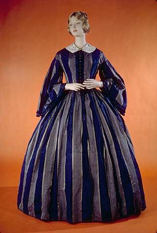 Day dress, 1861. Blue & tan striped silk, slightly dropped round neck edged with piping. Center front closure with blue glass buttons set in metal. Bodice lined in brown cotton, bell sleeves and skirt lined in blue cotton. Blue cotton watch pocket at left waist.