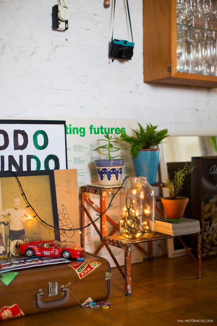Hall de entrada com quadros, peças vintage e vasinhos de plantas.