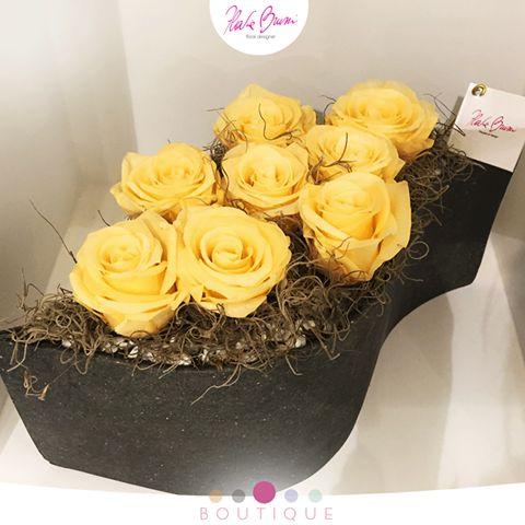 Una composizione con rose stabilizzate e tillandsia, raccolte in un contenitore ad onda, dalla selezione glamour della Boutique