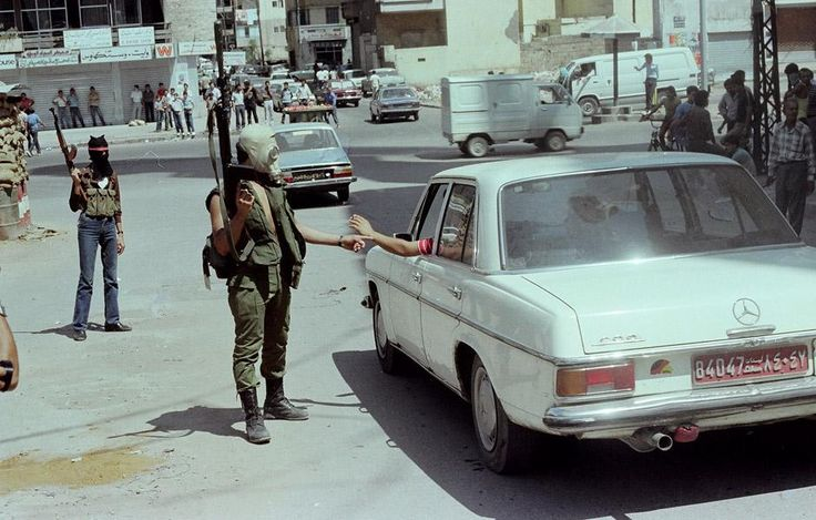 "Photos from Lebanon's Civil War (Photo: Ali Seifeddine) - ""Keep your hand on your ID card and squeeze it as tight as you can."" The photo is in West Beirut, as it was known at the time, and it shows a fighter from al-Mourabitoun checking the papers of the Mercedes driver. The car's red licence plate indicates that it was a cab. The photographer remembers that al-Mourabitoun fighters liked to take photos even though they wore masks fearing that they would be discovered when the war is over…"